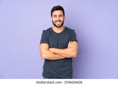 Caucasian handsome man keeping the arms crossed in frontal position over isolated purple background