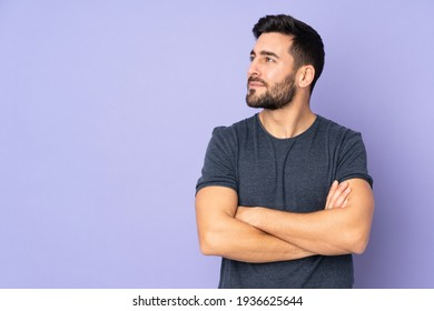 Caucasian handsome man looking to the side over isolated purple background