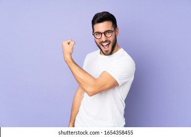 Caucasian handsome man over isolated background doing strong gesture
