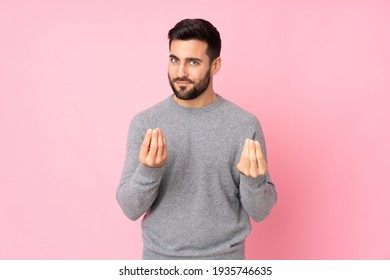 Caucasian handsome man over isolated background making money gesture but is ruined