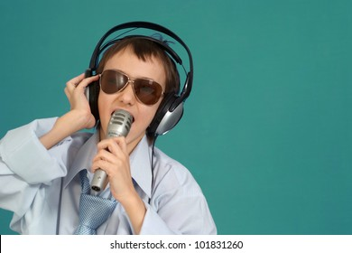 Caucasian handsome young boy with headphones posing on a turquoise background