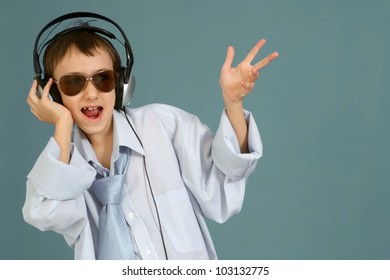 Caucasian handsome young guy with headphones posing on a turquoise background