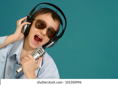 Caucasian handsome young lad with headphones posing on a turquoise background
