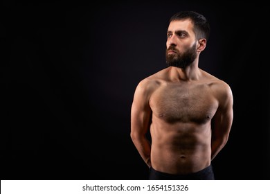 Caucasian handsome young man with a beard, serious, no shirt, muscular body,on black background looking sideways ahead, horizontal