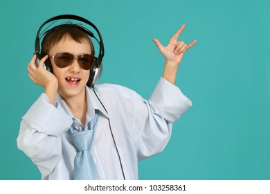 Caucasian handsome young man with headphones posing on a turquoise background