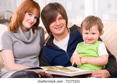 Caucasian happy family with toddler son in living room at sofa, smiling