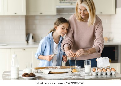 Caucasian happy mom and her beloved little daughter spend time together in the kitchen. Grandma teaches her cute granddaughter to cook pie, they are happy to cook together, having fun and laughing
