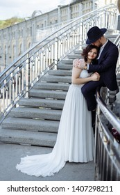 Caucasian happy romantic young couple of groom and bride on the stairs near river