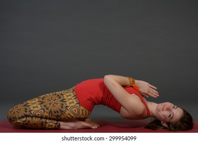 Caucasian healthy young fit sporty beautiful woman practicing yoga at photo studio on grey paper background.