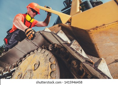 Caucasian Heavy Equipment Mechanic on a Bulldozer. Construction Site.