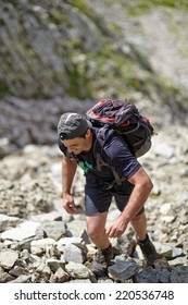 Caucasian hiker with backpack hiking into the mountains