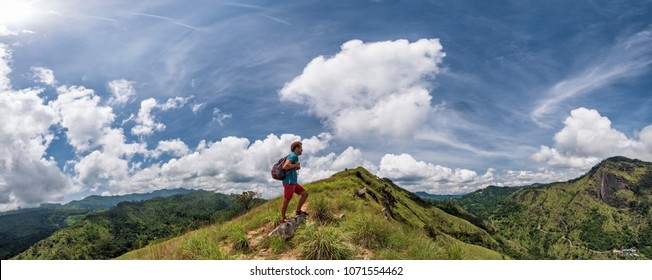 Caucasian hiker man take a rest on mountain peak with backpack. He is looking on beautiful landscape with blue sky and green hills. Panorama view