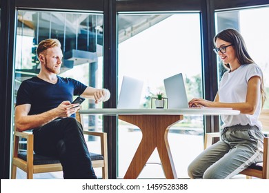 Caucasian hipster guy checking time on wearable smartwatch while female friend chatting online via application on laptop device, smiling woman searching positive movie for watching on leisure