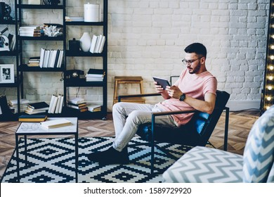 Caucasian hipster guy resting in comfortable flat with loft interior and using home free internet for installing application for communicate with friends in social network via digital tablet