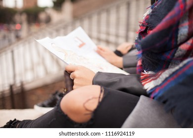 Caucasian hipster woman taking a break and reading map outside in the city.