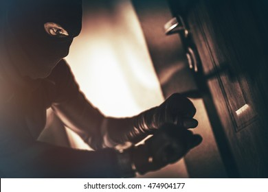 Caucasian House Burglar in Action. House Burglary Concept Photo. Home Safety Systems.