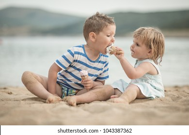 Caucasian kids eating ice cream at beash