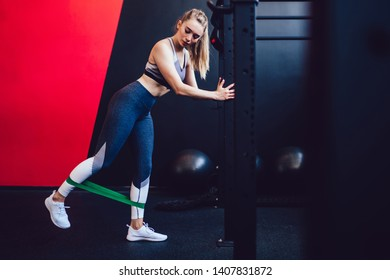 Caucasian lady doing fitness exercises with elastic band for training legs muscles concentrated on bodybuilding, attractive woman in trendy tracksuit using green expander