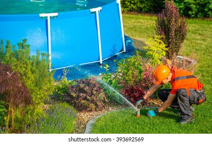 Caucasian Lawn Garden Technician in the Residential Garden with Swimming Pool Taking Care of Lawn Sprinklers System.