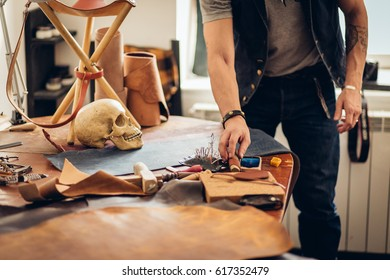 caucasian leather craft mustache man wearing cup working as artisan in his workshop