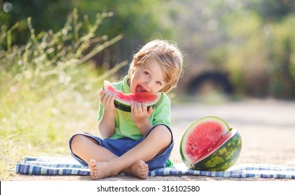 Caucasian little boy with blond hairs eating fresh watermelon in summer garden, outdoors. Kid eating red ripe watermelon