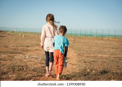 caucasian little boy and girl refugees walking alone in desert towards border with fence