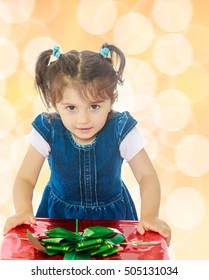 Caucasian little girl in a blue dress with short sleeves , kneeling around a red box with a bow. Close-up.Brown festive, Christmas background with white snowflakes, circles.