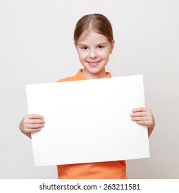 Caucasian little girl with white blank for advertisment