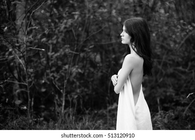 Caucasian long hair girl portrait in a  cloth at forest. Black and white.