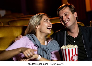 Caucasian lover enjoying to watch movie and eating popcorn together in the cinema