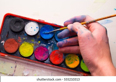 Caucasian Male artist hand using blue watercolor from palette