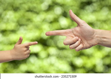 caucasian male and boy hand pointing, or gun gesture, on blurred natural green background