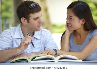 Caucasian male college students study together with asian female student