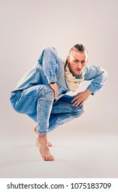 caucasian male dancer wearing blue denim shirt and pants on light background performing hip hop and contemporary style dance.