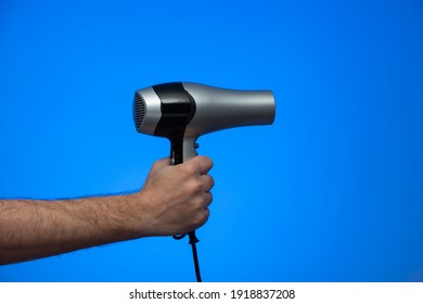 Caucasian male extended arm holding a hair dryer isolated on blue background studio shot.