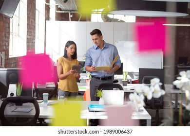Caucasian male and female colleague discuss tablet and file, view through glass wall and memo notes. working in business at a modern office.