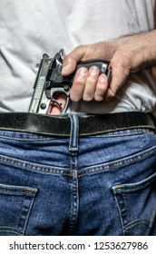 Caucasian male hand gripping a silver 9mm handgun in his waistband view from behind