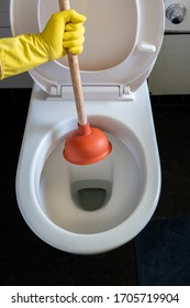 Caucasian male hand in yellow latex glove unclogging a clean toilet bowl with a plunger 2020