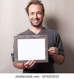A caucasian male holding a picture frame.