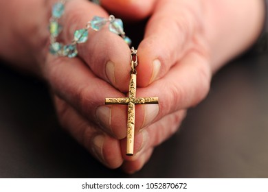 Caucasian male holding rosary beads with cross