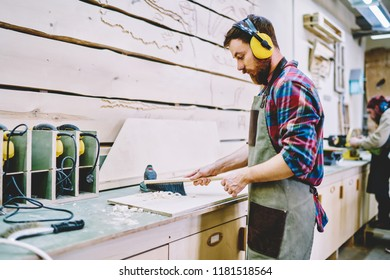 Caucasian male joiner in apron and headphones for safety and protection taking off sawdust after working with wood board, skilled foreman concentrated on timber carpentry in own craft wooden workshop