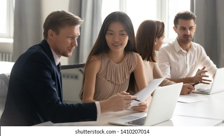 Caucasian male manager mentor teach consult asian female client intern about contract online project looking at laptop sit at desk in office, happy korean trainee customer learn new skills get advice