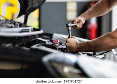 Caucasian male mechanic repairs car in garage. Car maintenance and auto service garage concept. Closeup hand and spanner.