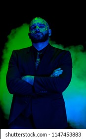 A caucasian male model with green blacklight paint. Paint resembles a circuit board. Dark suit with green accents. Glowing green smoke flowing behind the model