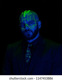A caucasian male model with green blacklight paint. Paint resembles a circuit board. Dark suit with green accents