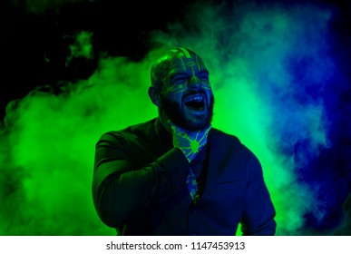 A caucasian male model with green blacklight paint screaming. Paint resembles a circuit board. Dark suit with green accents. Glowing green smoke flowing behind the model