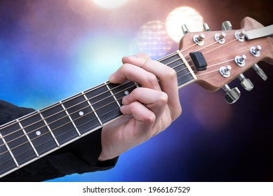 A Caucasian male musicians hand strikes a chord while in position on the neck of his electric guitar with stage lights setup in the background.