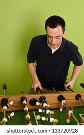 Caucasian male playing Foosball, table football / soccer