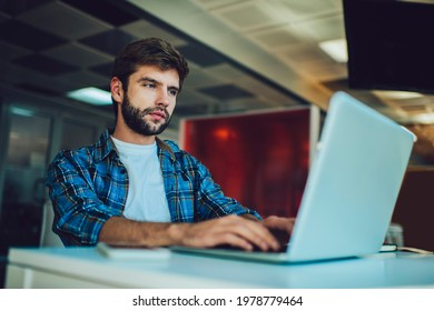 Caucasian male programmer creating software system via laptop application using coworking wifi internet, skilled man searching data code for editing during distance work on digital netbook