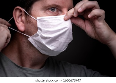 Caucasian male putting on a face mask with one hand putting the elastic band on an ear and with the other tighten the metal piece around the nose bridge